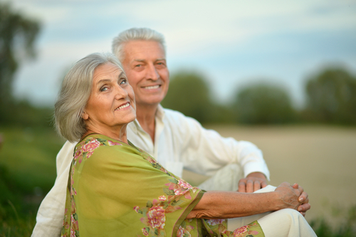 Elderly couple sitting outside smiling