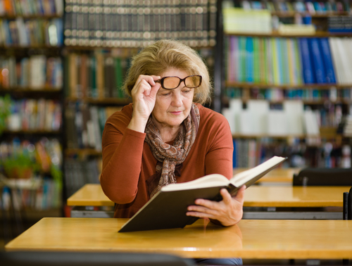 Women lifting up glasses to read book.